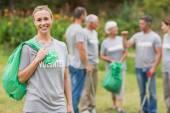 Happy volunteer collecting rubbish — Stock Photo