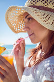 Brunette wearing straw hat and drinking a cocktail — Stock Photo