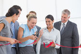 Happy business team cutting red ribbon — Stock Photo