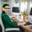 Smiling brunette working at her desk and listening music — Stock Photo #76362757