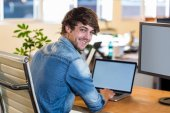 Smiling casual businessman sitting at desk — Stock Photo