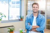 Casual businessman smiling at camera with arms crossed — Stock Photo