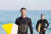 Men in wetsuits with surfboard at beach — Stock Photo