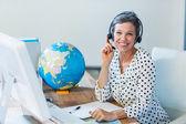 Agente de viajes sonriente sentada en su escritorio — Foto de Stock