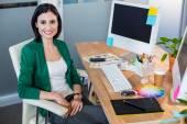 Smiling designer sitting at her desk — Stock Photo