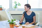 Smiling casual businesswoman working on digitizer — Stock Photo