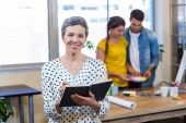 Příležitostné podnikatelka v deníku zatímco kolegové pracují — Stock fotografie