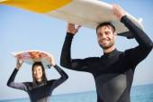 Couple in wetsuits with surfboard at beach — Stock Photo