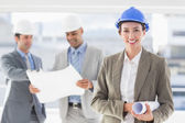 Businessmen and a woman with hard hats — Stock Photo
