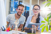 Smiling partners working together on tablet — Stock Photo