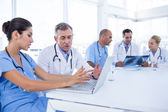 Doctors using computer whiles theirs colleagues looking at Xray — Stock Photo