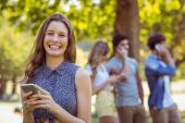 Happy friends in the park using their phones — Stock Photo