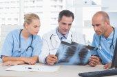 Doktor s kolegy při pohledu na Xray — Stock fotografie
