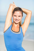 Beautiful fit woman stretching her arm — Stockfoto