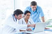 Team of doctors working on laptop — Stock Photo