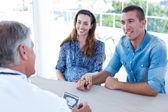 Doctor showing ultrasound scan to couple — Stock Photo