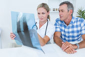 Doctor showing X rays to her patient — Stock Photo