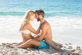 Happy couple relaxing together in the sand — Stock Photo