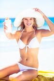 Pretty blonde woman holding sun tan lotion — Stock Photo