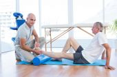 Trainer working with man on exercise mat — Stock Photo