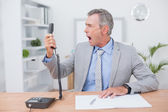 Irritated businessman answering phone — Stock Photo