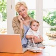 Woman with son phoning and using laptop — Stock Photo #76624449