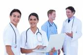 Doctors and nurses discussing and using laptop — Stock Photo