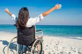 Disabled woman with arms outstretched at the beach — Stock Photo