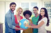 Young creative business people with a globe — Stock Photo
