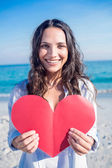 Smiling woman holding heart card at the beach — Stockfoto
