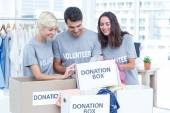 Volunteers friends checking a donation list — Stock Photo