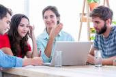 Creative business people using laptop in meeting — Stock Photo