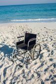 Black wheelchair on beach — Stock Photo