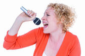 Happy blonde singing in microphone — Stock Photo