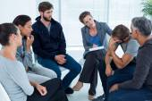 Concerned woman comforting another in rehab group — Stock Photo