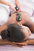 Woman enjoying hot stone massage — Foto Stock
