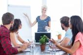 Casual businesswoman giving presentation to her colleagues — Stock Photo