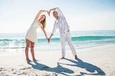 Happy couple forming heart shape with their hands — Stock Photo