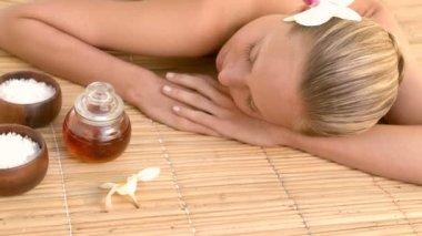 Woman enjoying a herbal compress massage — Stock Video