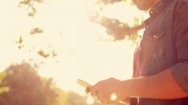 Muž svůj smartphone v parku — Stock video