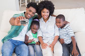 Happy family taking a selfie on the couch — Stock Photo