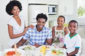 Happy family sitting down to dinner together — Stock Photo