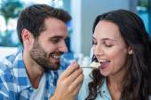Young happy couple feeding each other with cake — Stock Photo