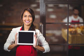 Smiling waitress showing a digital tablet — Stock Photo