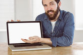 Hipster businessman showing his laptop — Stock Photo