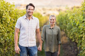 Two young happy vintners holding hands — Stock Photo