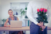 Man hiding bouquet in front of businesswoman — Stock Photo