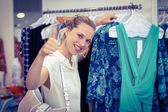 Woman browsing clothes and thumbs up — Stock Photo