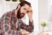 Hipster businessman stressed at his desk — Stock Photo