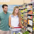 Bright couple buying products in aisle — Stock Photo #81850856